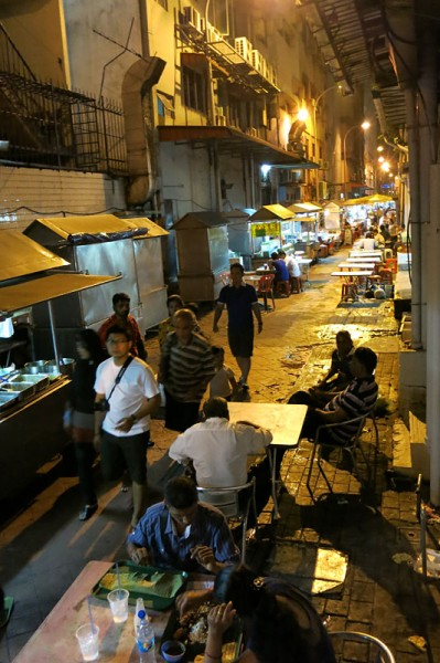 Small street in Johor Bahru with street food stalls and tables ...