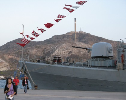 A military ship and a mountain fortress in the background