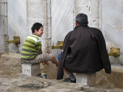Father and son washing feets outside a mosque