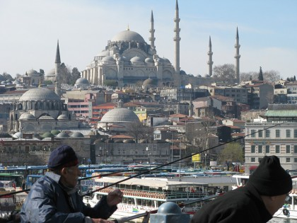Fishing on the Galata bridge with a mosque in the background