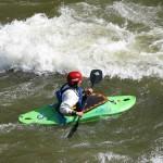 Green kayak in stream