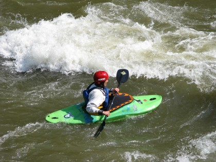 Green kayak in stream