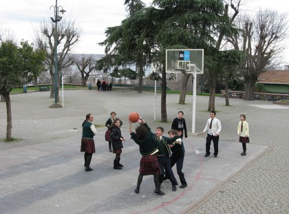 School children playing basket ball in a school yard